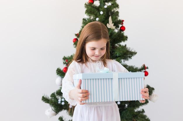 休日、プレゼント、クリスマス、クリスマスのコンセプト-ギフトボックスを持つ幸せな子の女の子。