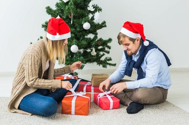 Праздники, отношения и праздничная концепция - пара вместе открывает подарок у елки