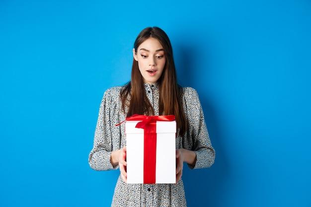 Праздники удивили молодую женщину, смотрящую на подарок с удивленным лицом, получают стенд подарка на день святого валентина ...