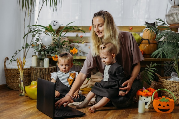 Holidays in the time of covid happy family mother and baby celebrating halloween via internet in new