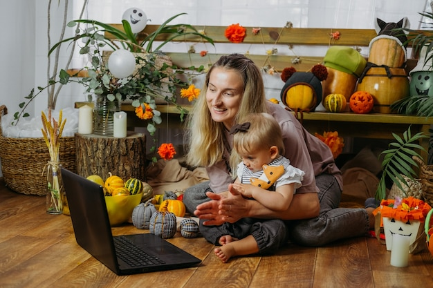Holidays in the time of covid. happy family, mother and baby celebrating halloween via internet