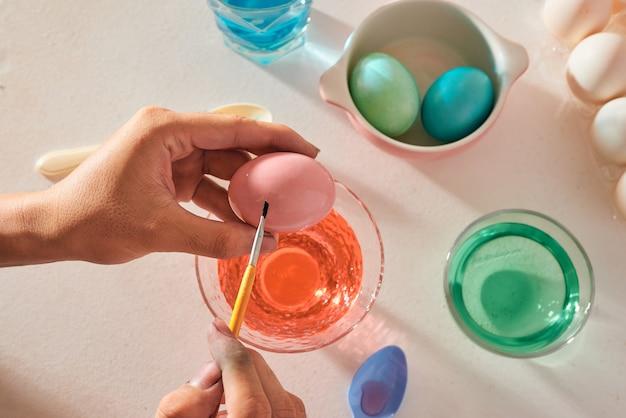 休日、伝統、人々の概念-ブラシでイースターの卵を着色する男の手のクローズアップ-