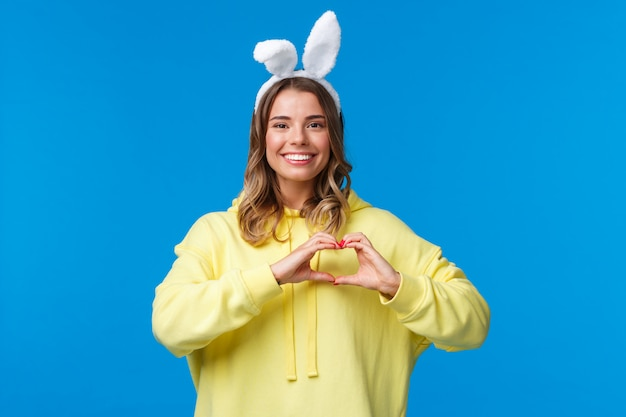 Holidays, traditions and celebration concept. waist-up portrait of charismatic cute blond girl in rabbit ears, congratulate everyone with easter holiday, show heart gesture and smiling