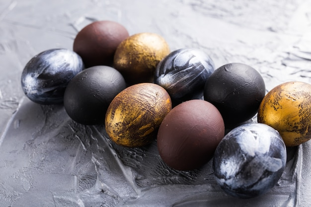 Holidays, traditions and easter concept - dark stylish easter eggs on grey background.