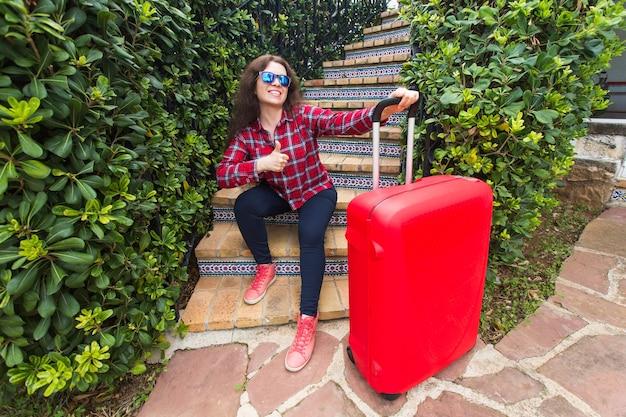 休日、旅行、人々の概念-スーツケースと笑顔で階段に座ってサングラスをかけた若い女性。