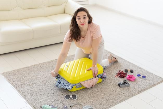 Праздники, путешествие и концепция путешествий - женщина собирает желтый чемодан дома.