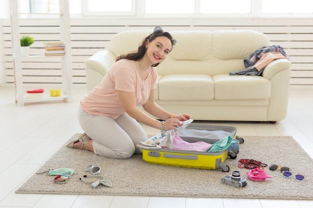 休日、航海、旅行のコンセプト-若い女性は自宅の寝室でスーツケース、たくさんのもの、休暇、黄色いスーツケースを集めます。