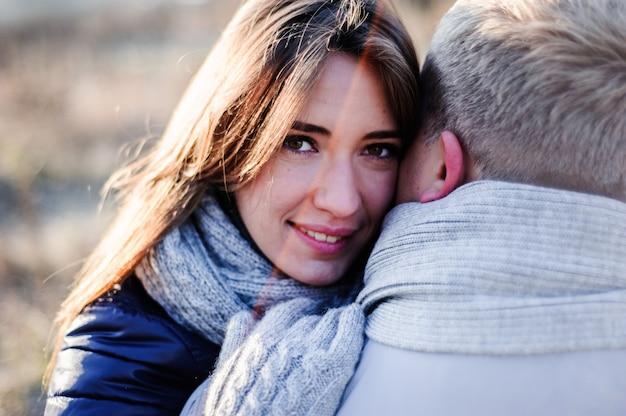 Праздники, зима, рождество, горячие напитки и люди концепции - счастливая пара в теплой одежде, обниматься возле веток деревьев со снегом