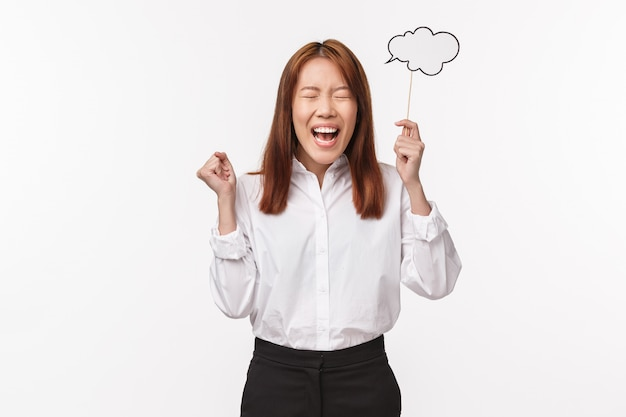 Holidays, women and lifestyle concept. portrait of cheerful happy smiling asian woman got inspired have perfect idea, holding comment cloud on stick and feeling excited, stand white wall