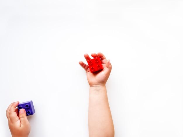 子供は拳で紫と赤のコンストラクタブロックをholidng