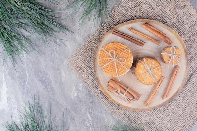 Голландские вафли и печенье на деревянной доске с палочками корицы вокруг.