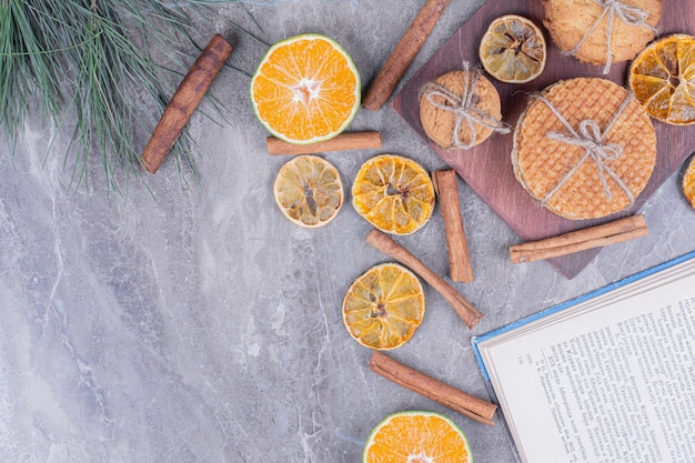 Holland waffles with cookies on a wooden board with dry orange slices and cinnamons around