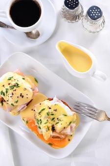 Голландский масляный соус в соуснике на завтрак подается с яйцами бенедикт - жареная английская булочка, ветчина, яйца пашот, чашка кофе.
