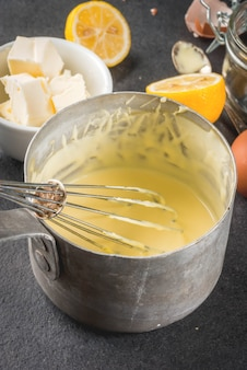 Hollandaise sauce in a metal saucepan, with ingredients for the recipe