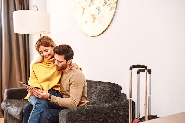 休日の計画。彼女のボーイフレンドの膝に座って夢を見ている若い女性。ホテルの部屋でタブレットを検索するスーツケースと幸せな成熟したカップル