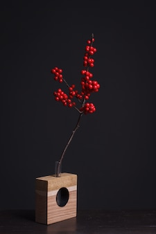 Holly branch with red berries in a wooden vase