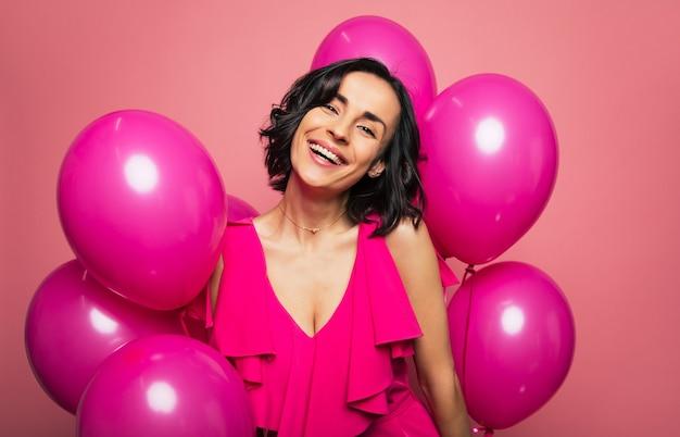 Голливудская улыбка. фотография крупным планом молодой очаровательной дамы в розовом платье, которая смеется от радости в окружении розовых воздушных шаров.