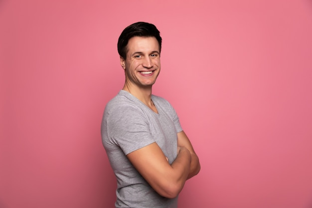 Hollywood smile. young happy man in a grey t-shirt, who is standing in semi-profile with folded arms and smiling confidently.