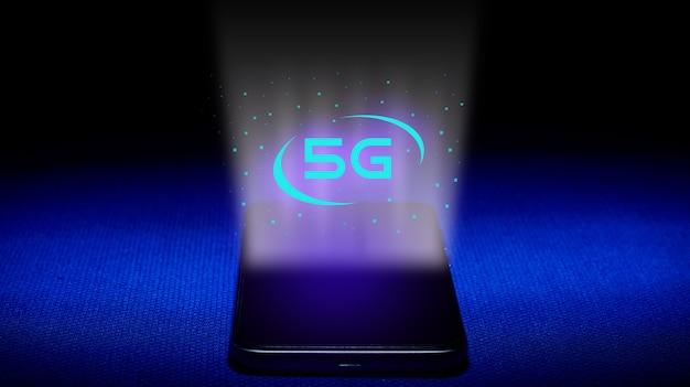 5gのホログラム。スマートフォンと青い背景の5gホログラム画像。 5gテクノロジーのコンセプトは新世代のネットワークです。 -画像