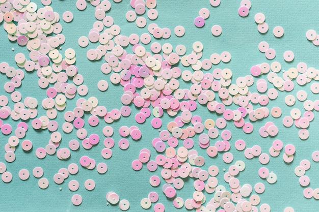 Голографическое пастельное конфетти на синем фоне. творческий праздничный фон.