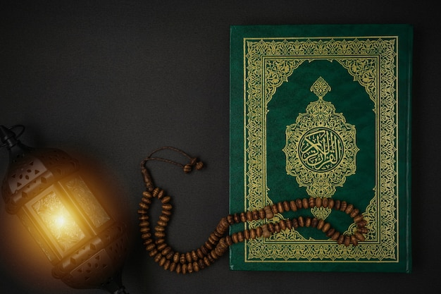 Holy al quran with written arabic calligraphy meaning of al quran and rosary beads on black