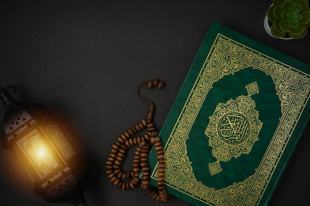 Holy al quran with written arabic calligraphy meaning of al quran and rosary beads
