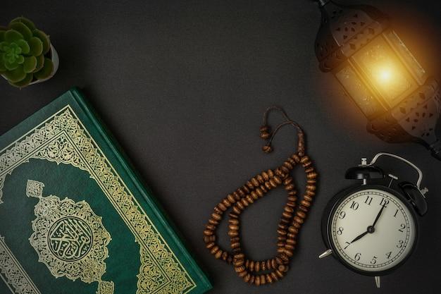 黒にアルコーランとロザリオビーズのアラビア語の書道の意味が書かれた聖なるアルコーラン