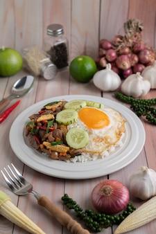 Священный базилик жареный рис с куриным сердцем и жареным яйцом на белом деревянном полу.