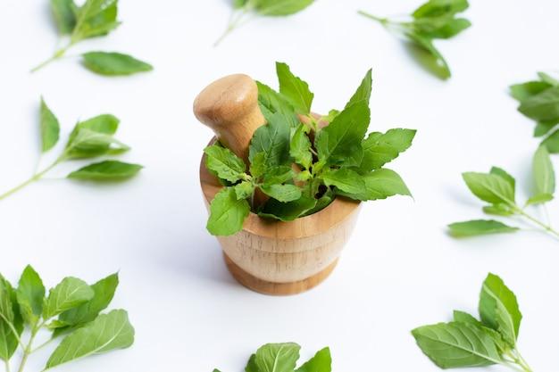 乳棒と木製の乳鉢で聖なるバジルの葉
