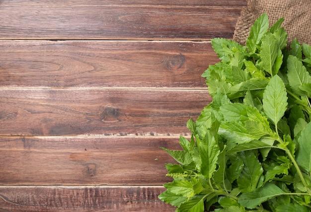 木製の背景に聖バジルの葉、スペースをコピー