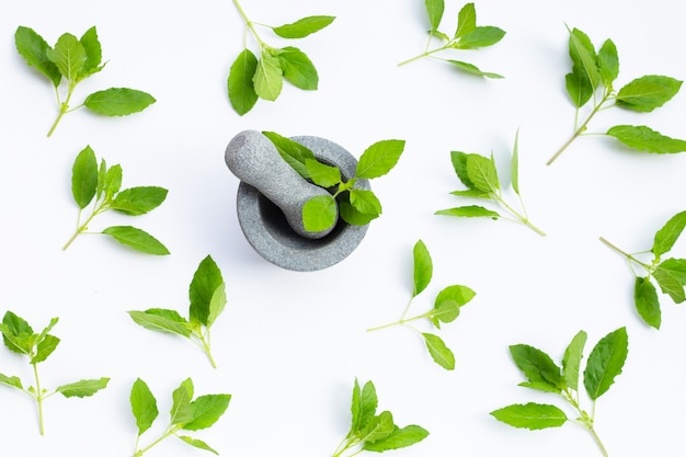 Holy basil leaves in rock mortar with pestle on white surface