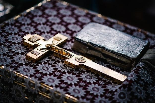 聖書と教会の聖体礼儀のテーブルの上の十字架