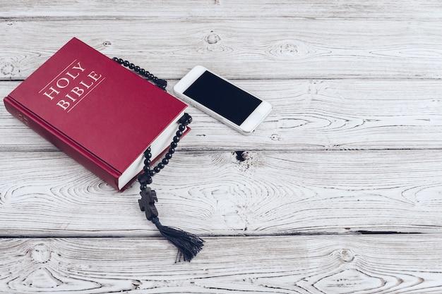聖書と木製の表面にブラックコーヒーカップを持つスマートフォン。