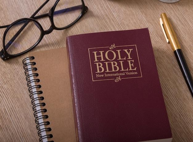성경, 노트북, 안경 및 펜 책상에
