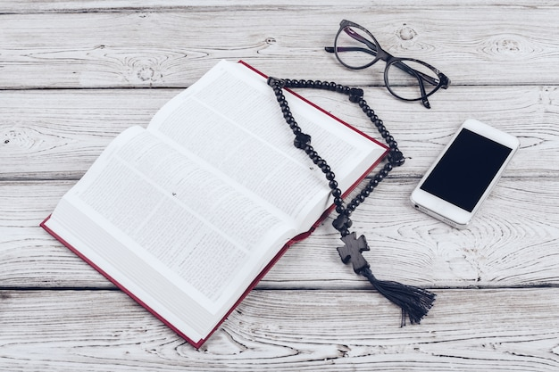 Holy bible and smartphone with black coffee cup on wood.