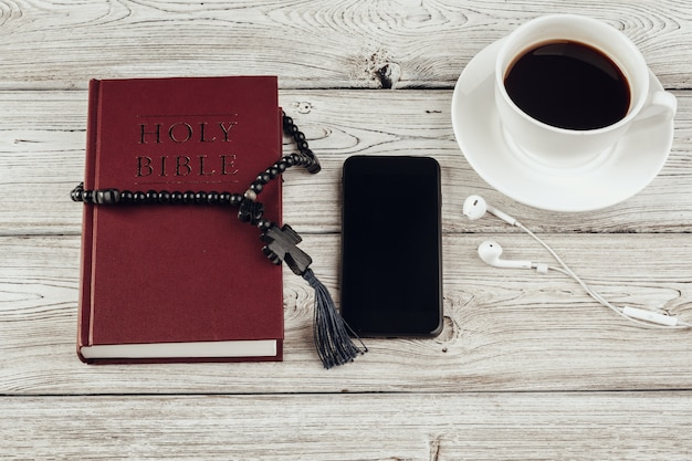Holy bible and smartphone with black coffee cup