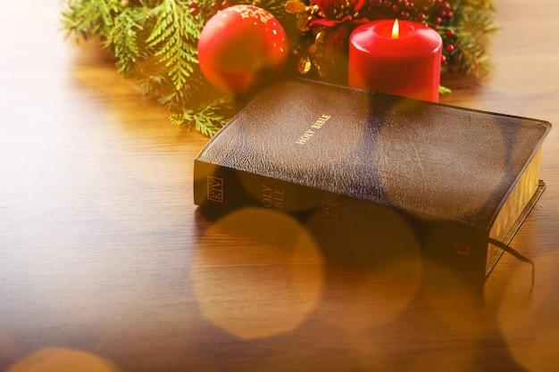큰 빨간 촛불과 크리스마스 장식이 있는 성경