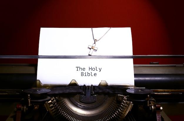 ヴィンテージタイプライターによって紙に書かれた聖書。クロスネックレス。