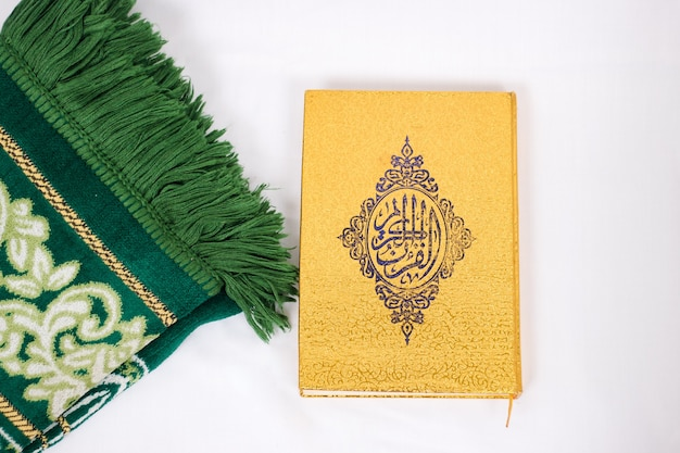 The holy book al quran and prayer rug isolated on white background