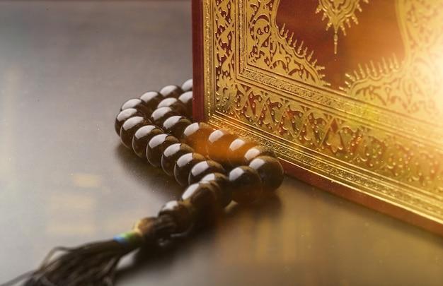 Священная книга и бусы на столе, крупным планом