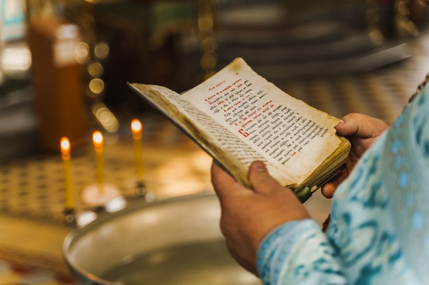 Holy book opened in priest hands in church