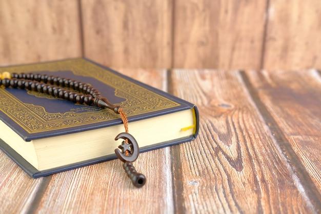 聖典コーランとテーブルの上の数珠のクローズアップ