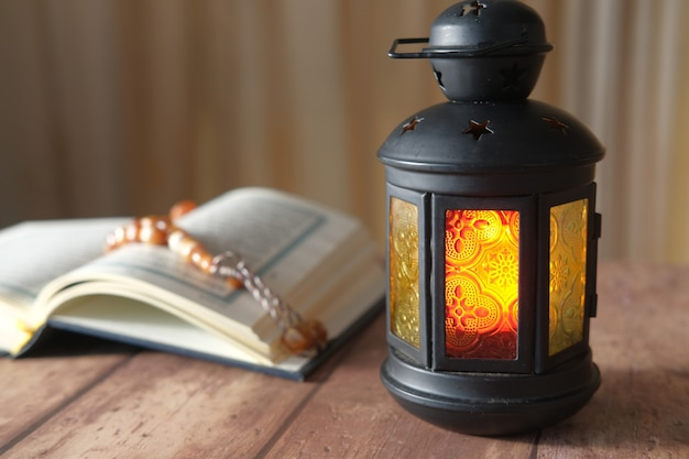 聖典コーラン、ロザリオ、テーブルの上の革のランプ