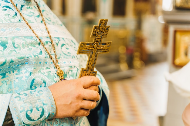 Holy father in his robe with a golden cross in his hands in church