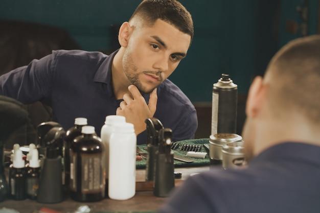 Святая жара. портрет привлекательного мужчины клиента, проверяя его бороду и прическу, глядя в зеркало в парикмахерской