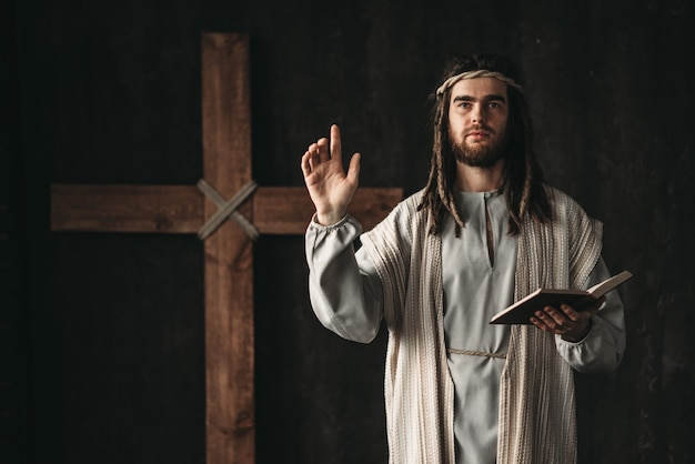 Holy jesus christ praying with biblical in hands, cross on black