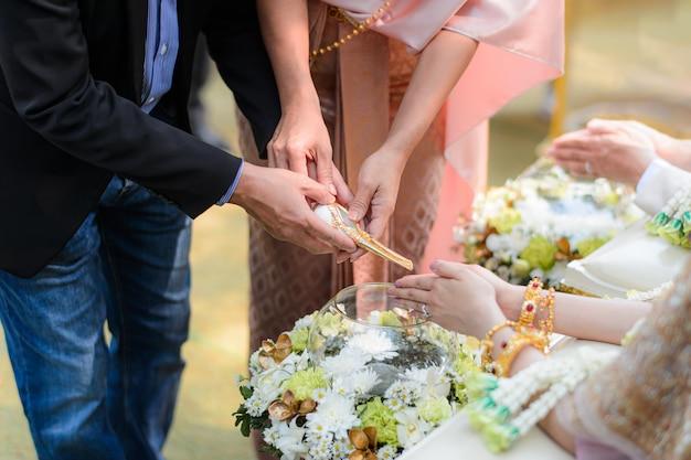 新郎新婦のタイの結婚式の婚約のための聖水を注ぐ式