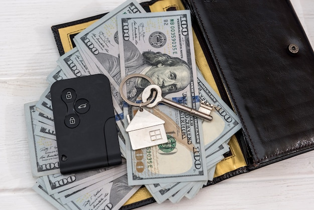 테이블에 달러 지폐와 homa nad 자동차 키. 절약 개념