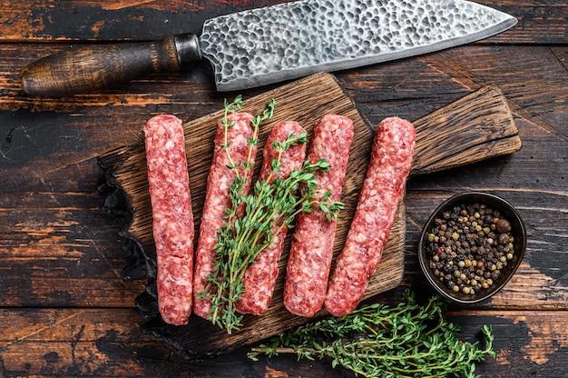 Homamade сырое мясо, люля-кебаб, колбаски на разделочной доске.