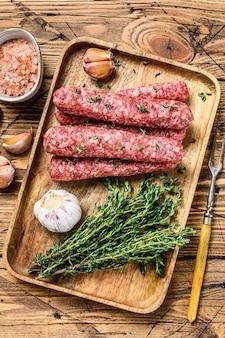 まな板にのせた生ミンチ肉ソーセージ。木製の背景。上面図。